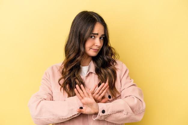 Jeune femme caucasienne isolée sur fond jaune faisant un geste de déni