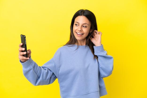 Jeune femme caucasienne isolée sur fond jaune faisant un selfie