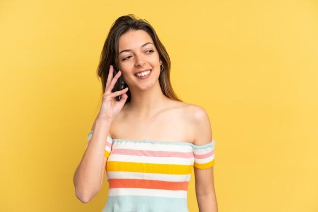 Jeune femme caucasienne isolée sur fond jaune gardant une conversation avec le téléphone portable avec quelqu'un
