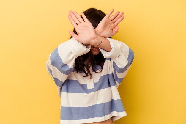 Jeune femme caucasienne isolée sur fond jaune en gardant les deux bras croisés, concept de déni.
