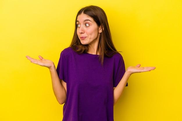 Jeune femme caucasienne isolée sur fond jaune, haussant les épaules confuse et douteuse pour tenir un espace de copie.