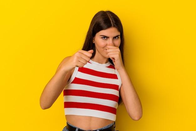 Jeune femme caucasienne isolée sur fond jaune jetant un coup de poing, colère, combat à cause d'une dispute, boxe.