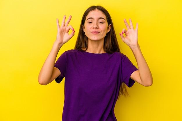 Jeune femme caucasienne isolée sur fond jaune se détend après une dure journée de travail, elle fait du yoga.