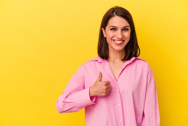 Jeune femme caucasienne isolée sur fond jaune souriant et levant le pouce vers le haut