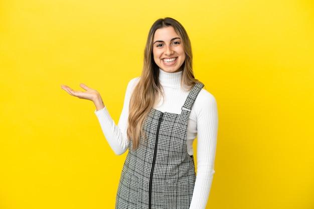 Jeune femme caucasienne isolée sur fond jaune tenant un espace de copie imaginaire sur la paume pour insérer une annonce