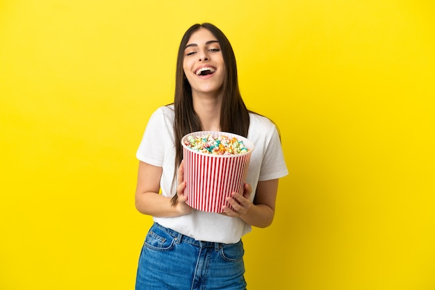 Jeune femme caucasienne isolée sur fond jaune tenant un grand seau de pop-corn