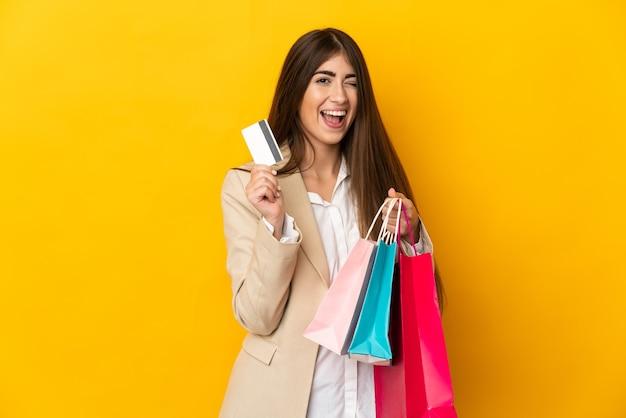 Jeune femme caucasienne isolée sur fond jaune tenant des sacs à provisions et une carte de crédit