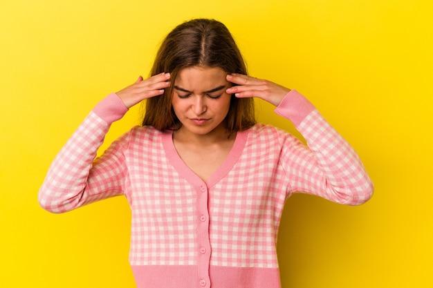 Jeune femme caucasienne isolée sur fond jaune touchant les temples et ayant des maux de tête.