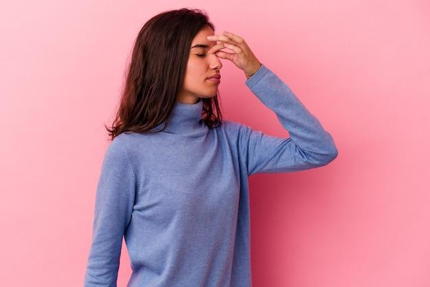 Jeune femme caucasienne isolée sur fond rose ayant un mal de tête, touchant le devant du visage.