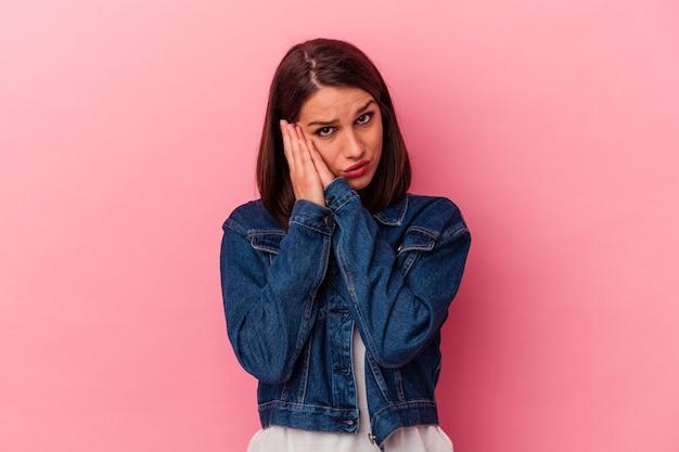 Jeune femme caucasienne isolée sur fond rose bâillant montrant un geste fatigué couvrant la bouche avec la main.