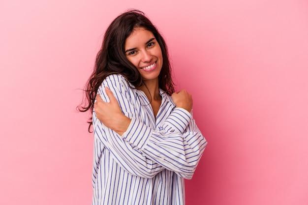 Jeune femme caucasienne isolée sur fond rose câlins, souriante insouciante et heureuse.