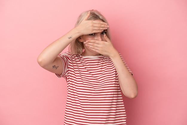 Jeune femme caucasienne isolée sur fond rose cligne des yeux vers la caméra à travers les doigts, embarrassée pour couvrir le visage.