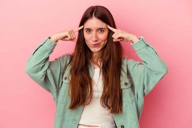 Jeune femme caucasienne isolée sur fond rose concentrée sur une tâche, gardant les index pointant la tête.
