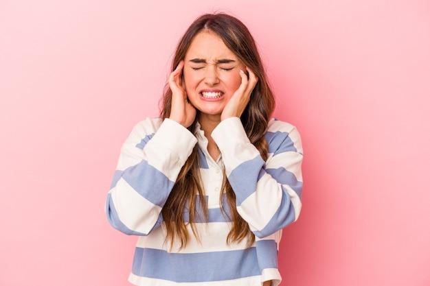 Jeune femme caucasienne isolée sur fond rose couvrant les oreilles avec les mains.