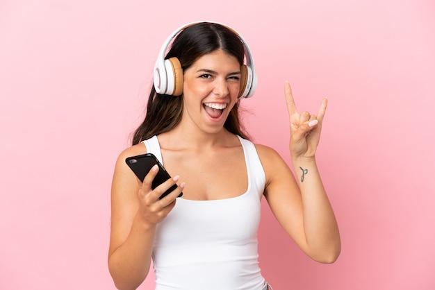 Jeune femme caucasienne isolée sur fond rose écoutant de la musique avec un mobile faisant un geste rock