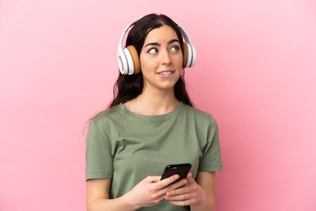 Jeune femme caucasienne isolée sur fond rose, écoutant de la musique avec un mobile et pensant