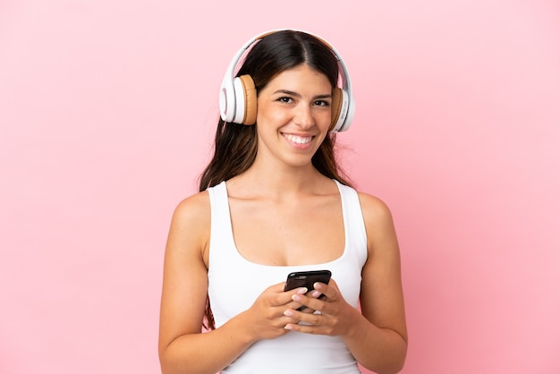 Jeune femme caucasienne isolée sur fond rose, écoutant de la musique avec un mobile et regardant à l'avant