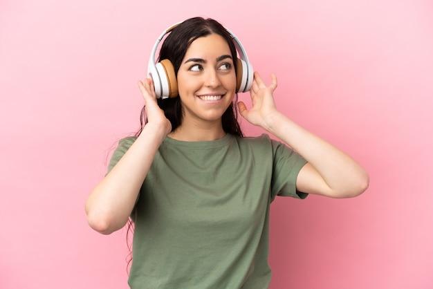Jeune femme caucasienne isolée sur fond rose à l'écoute de la musique