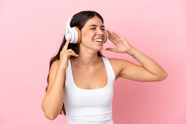 Jeune femme caucasienne isolée sur fond rose, écouter de la musique et chanter