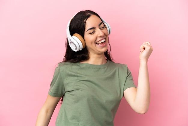 Jeune femme caucasienne isolée sur fond rose, écouter de la musique et de la danse