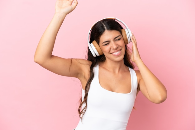 Jeune femme caucasienne isolée sur fond rose, écouter de la musique et danser