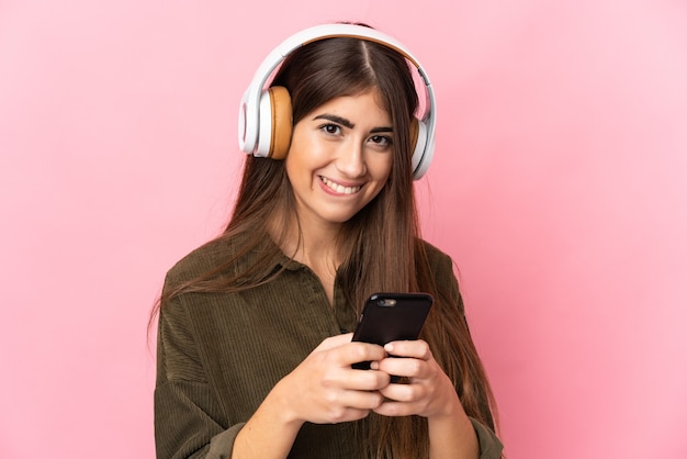 Jeune femme caucasienne isolée sur fond rose, écouter de la musique avec un mobile et à l'avant
