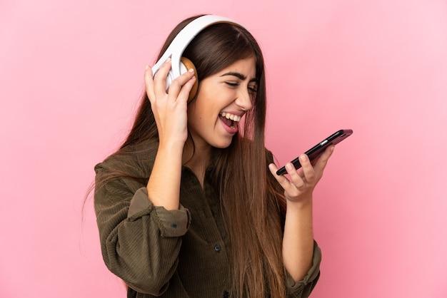 Jeune femme caucasienne isolée sur fond rose, écouter de la musique avec un mobile et chanter