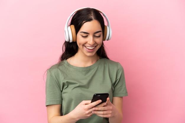 Jeune femme caucasienne isolée sur fond rose, écouter de la musique et à la recherche de mobile