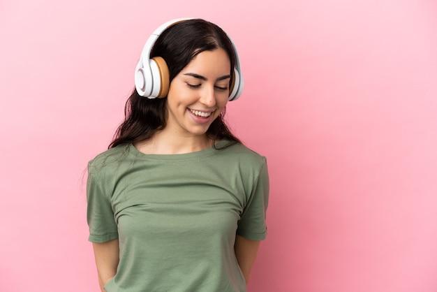 Jeune femme caucasienne isolée sur fond rose, écouter de la musique