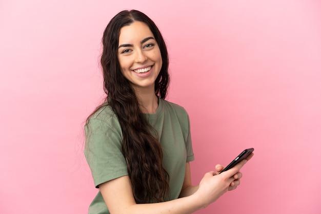Jeune femme caucasienne isolée sur fond rose, envoyer un message ou un e-mail avec le mobile