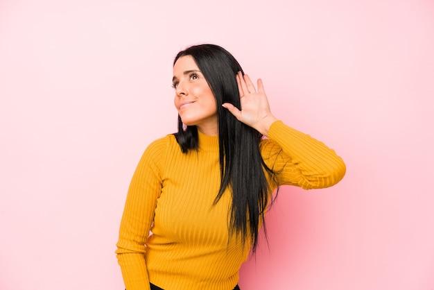 Jeune femme caucasienne isolée sur fond rose essayant d'écouter un potin.