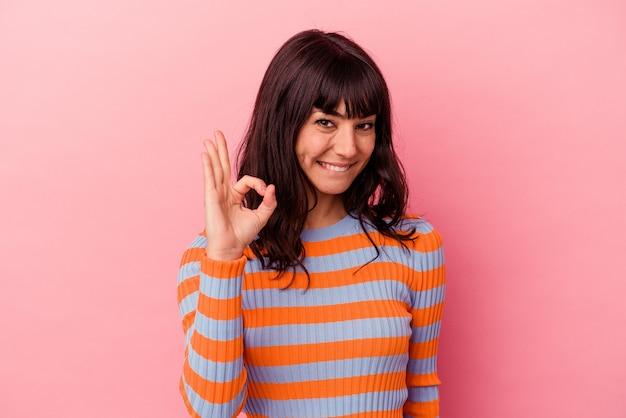 Jeune femme caucasienne isolée sur fond rose fait un clin d'œil et tient un geste correct avec la main.