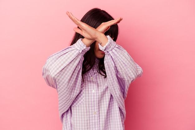 Jeune femme caucasienne isolée sur fond rose en gardant les deux bras croisés, concept de déni.