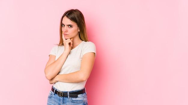 Jeune femme caucasienne isolée sur fond rose malheureux à la recherche à huis clos avec une expression sarcastique.