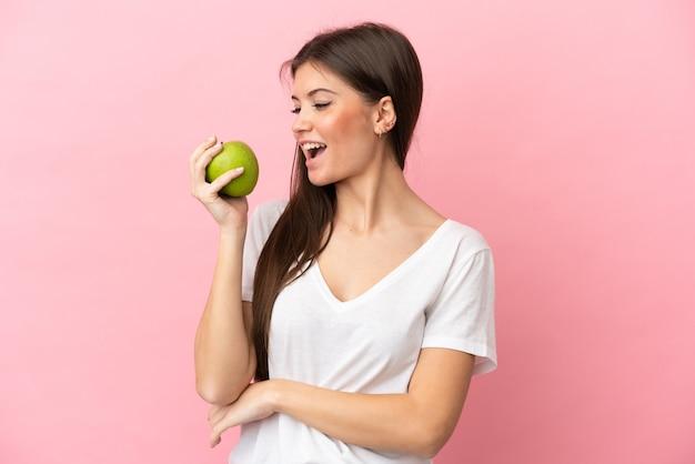 Jeune femme caucasienne isolée sur fond rose, manger une pomme
