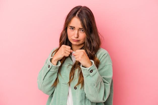 Jeune femme caucasienne isolée sur fond rose montrant le poing à la caméra, expression faciale agressive.