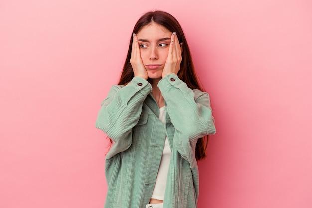 Jeune femme caucasienne isolée sur fond rose pleurnichant et pleurant de manière inconsolable.