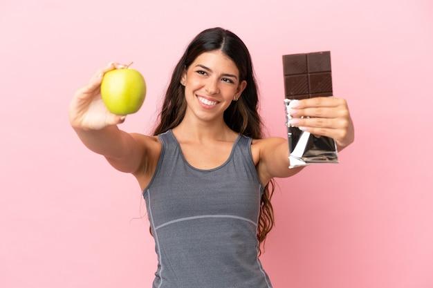 Jeune femme caucasienne isolée sur fond rose prenant une tablette de chocolat dans une main et une pomme dans l'autre