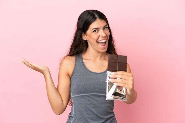 Jeune femme caucasienne isolée sur fond rose prenant une tablette de chocolat et surprise