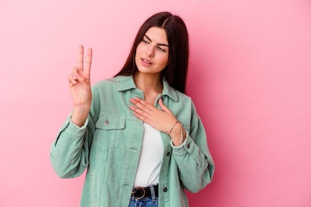 Jeune femme caucasienne isolée sur fond rose en prêtant serment, mettant la main sur la poitrine.