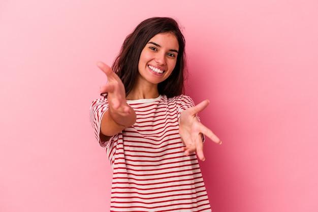 Jeune femme caucasienne isolée sur fond rose se sent confiante en donnant un câlin à la caméra.