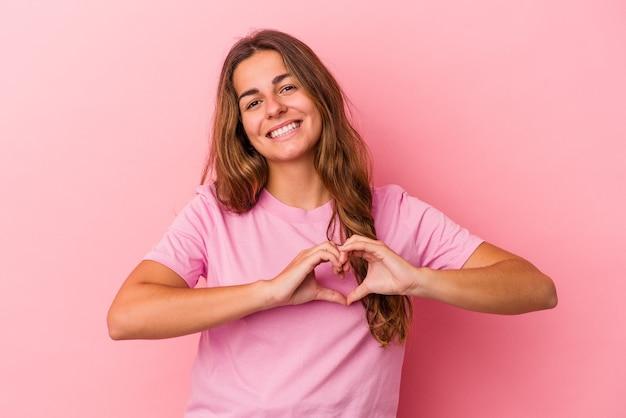 Jeune femme caucasienne isolée sur fond rose souriant et montrant une forme de coeur avec les mains.