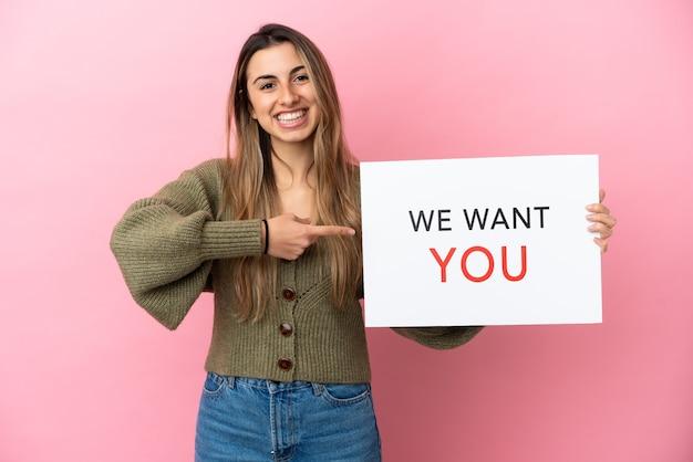Jeune femme caucasienne isolée sur fond rose tenant le panneau we want you et le pointant