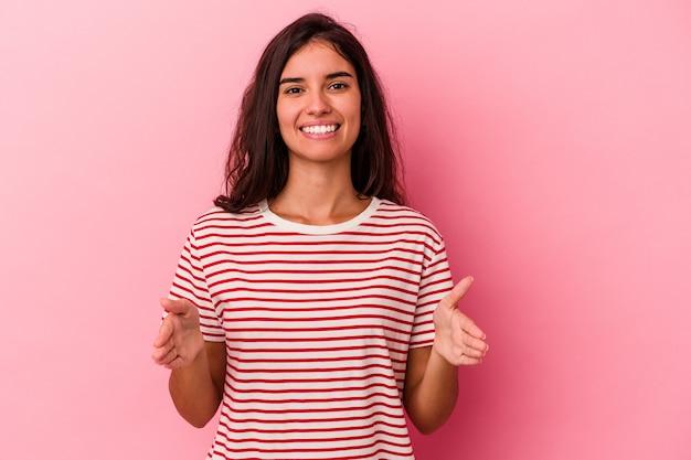 Jeune femme caucasienne isolée sur fond rose tenant quelque chose à deux mains, présentation du produit.