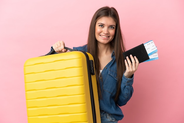 Jeune femme caucasienne isolée sur fond rose en vacances avec valise et passeport