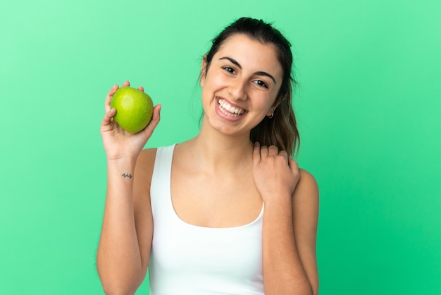 Jeune femme caucasienne isolée sur fond vert avec une pomme et heureuse