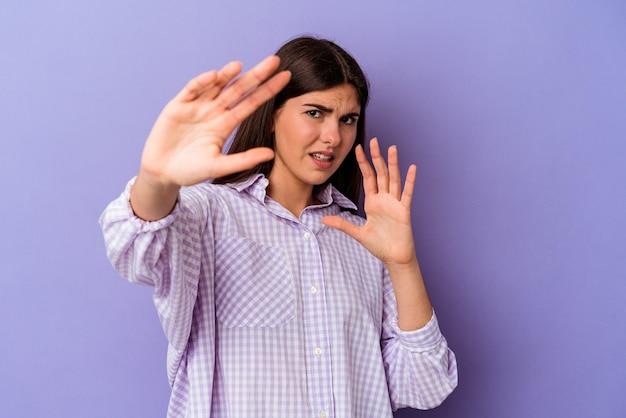 Jeune femme caucasienne isolée sur fond violet choquée en raison d'un danger imminent