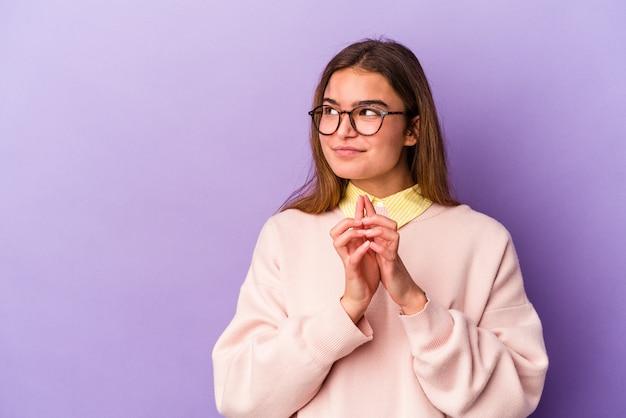 Jeune femme caucasienne isolée sur fond violet, élaboration d'un plan à l'esprit, mise en place d'une idée.