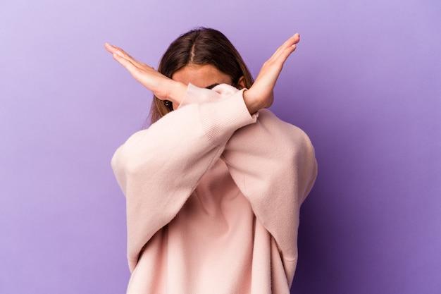 Jeune femme caucasienne isolée sur fond violet en gardant les deux bras croisés, concept de déni.