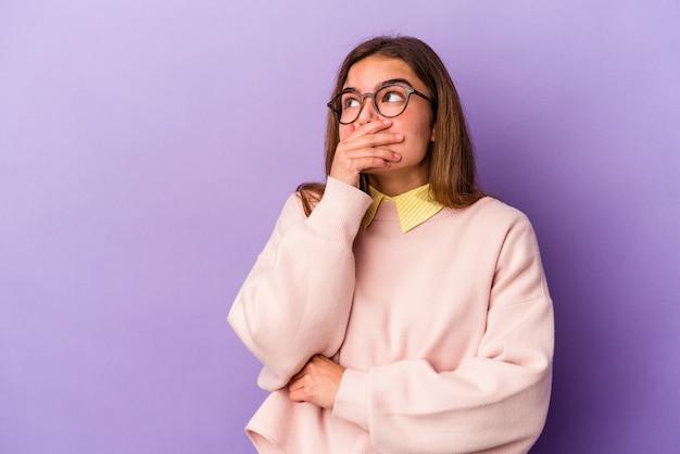 Jeune femme caucasienne isolée sur fond violet réfléchie à la recherche d'un espace de copie couvrant la bouche avec la main.